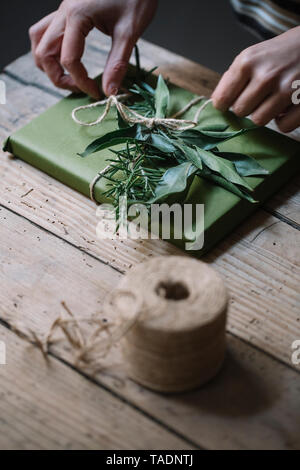 Woman's hands decorating present - Stock Photo