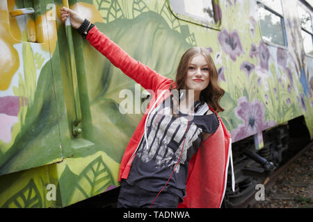 Portrait of teenage girl grimacing at a painted train car - Stock Photo