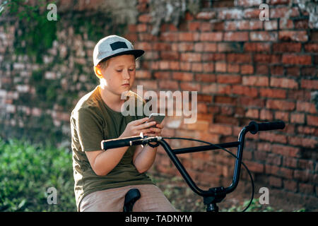 Boy with bmx bike using cell phone - Stock Photo