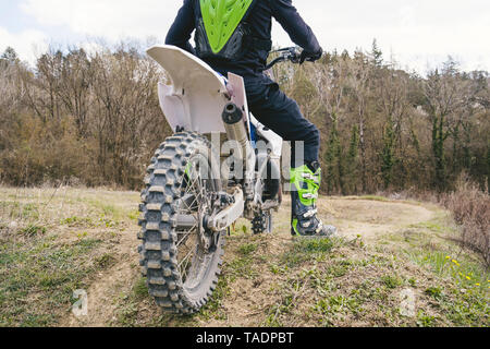 Close-up of motocross driver standing on circuit - Stock Photo