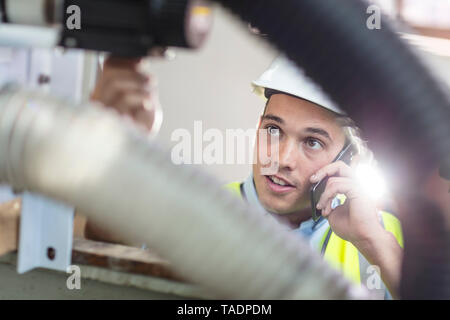 Technician at work talking on cell phone - Stock Photo