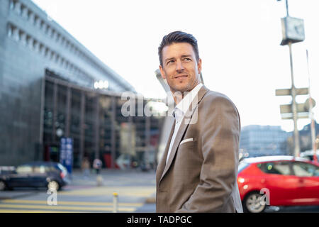 Smiling businessman on the move in the city - Stock Photo