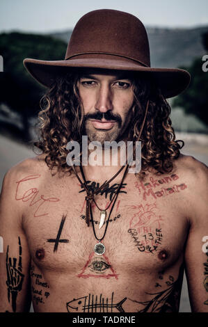Young man with hat, tattoos and mustache - Stock Photo