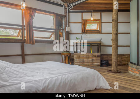 White Bed and Sink in Country Interior Design Room. Interior design room include glass bathroom faucet bamboo shelf and windows and curtain and chair. - Stock Photo