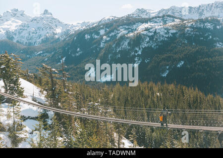 Father and son walking on a suspension bridge in the mountains, Squamish, Canada - Stock Photo