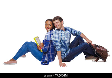 Side view of a couple of students who are sitting on the floor with their backs. Isolated over white background. Students are flirting sitting on the  - Stock Photo