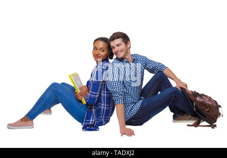Side view of a couple of students who are sitting on the floor with their backs. Isolated over white background. Students sitting on the floor look at - Stock Photo