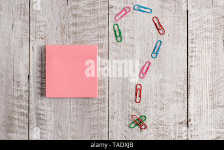 Pastel colour note paper placed next to stationary above the wooden table - Stock Photo