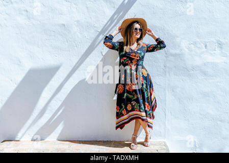 Spain, Cadiz, Vejer de la Frontera, fashionable woman with straw hat standing in front of white wall - Stock Photo
