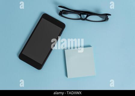 Dark eyeglasses colored sticky note smartphone fashion pastel background - Stock Photo