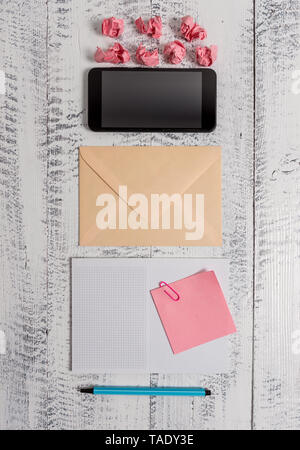 Envelop smartphone notepad note clip marker paper balls wooden background - Stock Photo