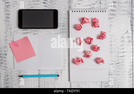 Squared spiral notebook marker smartphone paper balls note clip wooden - Stock Photo