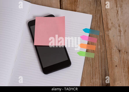 Note book four arrow banners smartphone sticky note old wooden background - Stock Photo