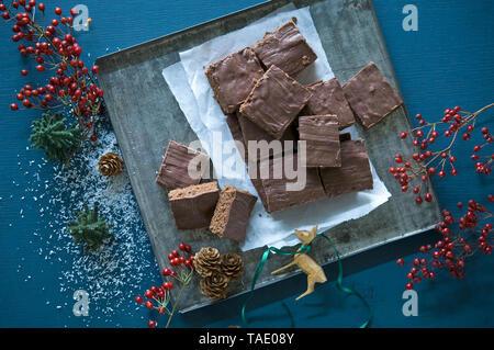 Home-baked sliced chocolate cake on baking tray - Stock Photo