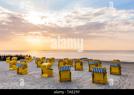 Germany, Lower Saxony, Cuxhaven, Duhnen, beach with hooded beach chairs at sunrise - Stock Photo