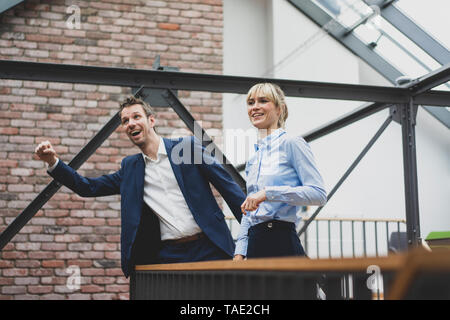 Businessman and woman standing in office building, discussing - Stock Photo