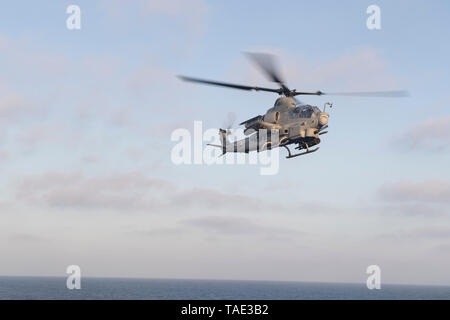 190506-N-NB544-1203 PACIFIC OCEAN (May 6, 2019) An AH-1Z Viper assigned to Marine Medium Tiltrotor Squadron (VMM) 163 (Reinforced), flies over the San Antonio-class amphibious transport dock ship USS John P. Murtha (LPD 26). Sailors and Marines of the Boxer Amphibious Ready Group (ARG) and 11th Marine Expeditionary Unit (MEU) are embarked on USS John P. Murtha on a regularly-scheduled deployment. (U.S. Navy Photo by Mass Communication Specialist 2nd Class Kyle Carlstrom) - Stock Photo