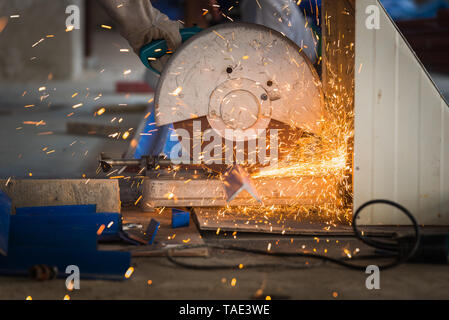 Industrial worker cutting metal with many sharp sparks. Selection focus to cutting machine. - Stock Photo