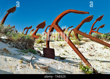 Dozens of anchors lying in sand dune contrasting with blue sky - Stock Photo