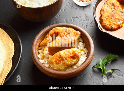 Fish curry with rice in wooden bowl on black stone table. Indian style food. - Stock Photo