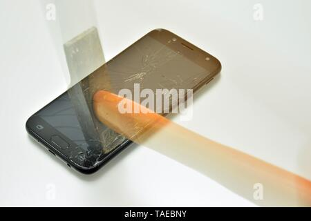 Martillo rompiendo la pantalla de un telefono movil - Stock Photo