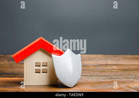 House figurine and protective shield. The concept of home security and safety. Alarm systems. The inviolability of private property, protection agains - Stock Photo