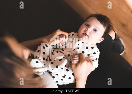 Funny baby lying on mother hands in room. Looking at camera. Top view. Childhood. - Stock Photo