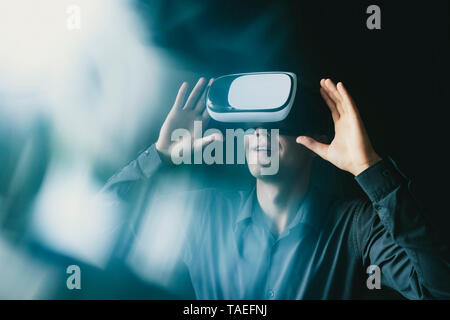 Composite image of a man wearing a VR headset interacting with a simulated virtual reality environment with light flare - Stock Photo
