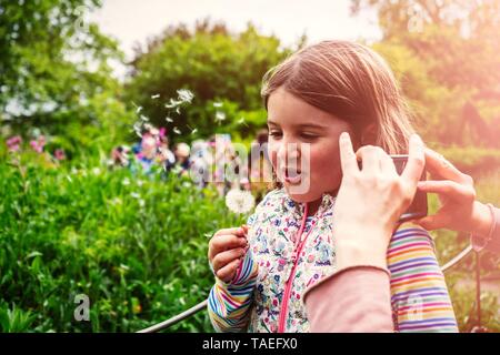 Cheerful mother taking picture of her cute little daughter in the park blowing dandelion - Stock Photo