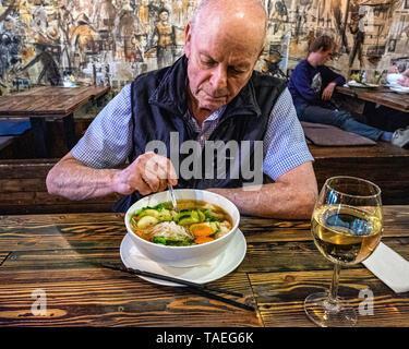 Fam Dang Vietnamese restaurant interior in Torstasse, Mitte-Berlin. Senior elderly man eating bowl of soup - Stock Photo