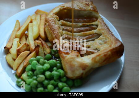 Toad in the hole (sausages baked in batter, England) - Stock Photo