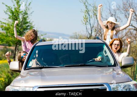 Female rioters behind the wheel, hooligans in the car showing gestures all around - Stock Photo