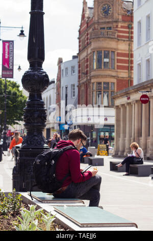 Young man sitting on busy high street, eating sandwich while checking mobile phone - Stock Photo
