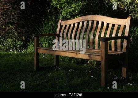 Garden bench on grass in English country garden during Spring - Stock Photo