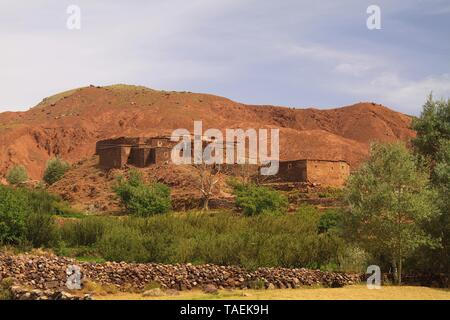 Old berber village oasis with houses build of clay bricks in front of impressive high rugged red mountain face, Gorges du Dades, Morocco - Stock Photo