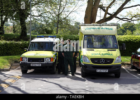 Two emergency ambulance vehicles parked next to each other with paramedics talking outdoors - Stock Photo