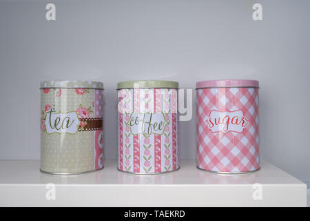 Tea coffee and sugar canisters or jars on a white kitchen bench - Stock Photo