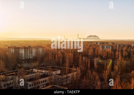 Cityscape view of Pripyat, Ukraine, inside the Chernobyl Exclusion Zone, with the Chernobyl Reactor in the background - Stock Photo