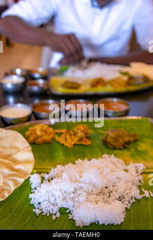Vertical view of a typical vegetarian thali meal being eaten with hands in India. - Stock Photo