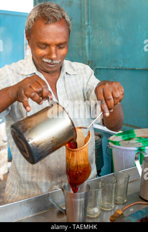 Vertical portrait of a man making traditional tea or chai in India. - Stock Photo