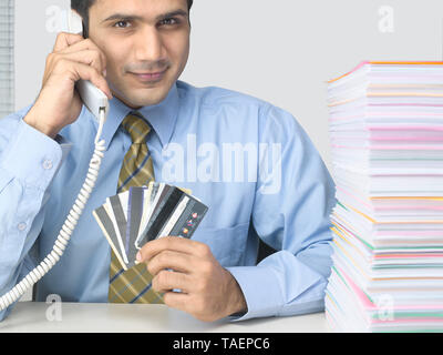 CORPORATE EXECUTIVE HOLDING MULTIPLE CREDIT CARDS WITH A HEAP OF PAPERS ON HIS DESK - Stock Photo