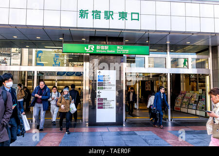 Tokyo, Japan - April 2, 2019: Shinjuku modern glass building JR rail station entrance architecture during day with many people walking at exit - Stock Photo