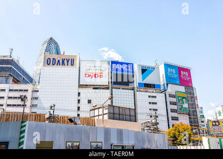 Tokyo, Japan - April 2, 2019: Shinjuku colorful cityscape during day with signs for Odakyu mall and shops stores - Stock Photo