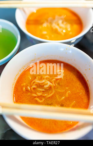 Macro closeup of spicy red ramen noodle soup bowl with chopsticks Japanese asian meal and green tea - Stock Photo