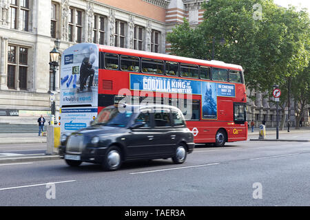 Godzilla King of the monsters Advertised on a London Bus as a black cab passes by - Stock Photo