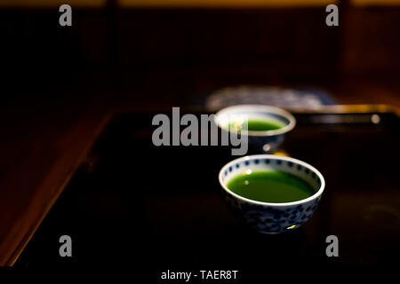 Traditional japanese cups with matcha or mulberry green tea in ryokan with black lacquered wood table - Stock Photo