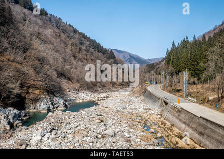 Japan rural area in Gifu prefecture, Hida with Miyagawa river green colorful water in mountains during spring and high angle view of road - Stock Photo