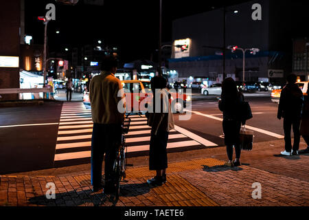 Kyoto, Japan - April 9, 2019: People waiting to cross street in Gion district at night with traffic cars and red light - Stock Photo