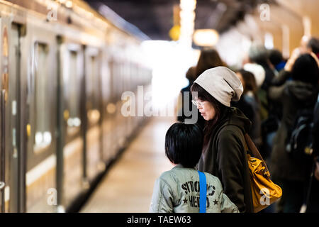 Utsunomiya, Japan - April 4, 2019: Train station platform local line to Nikko with many people waiting with Japanese mother and child - Stock Photo