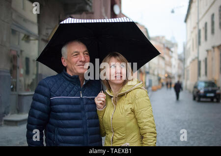 Close up portrait of elderly man and his young blonde-haired wife embracing each other and standing under their umbrella on paved street. Couple with  - Stock Photo